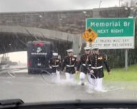 Woman Stuck in Flood Can't Believe Her Eyes as Cadre of Marines in Dress Blues Begins Wading to Her